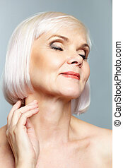 Delight - Portrait of aged female in delight over grey...