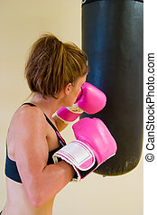 Punching W/ Pink Gloves 3 - Young woman in pink boxing...