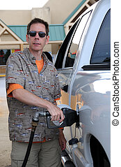 Pumping Gas - A man pumping fuel into a gas guzzling pickup...