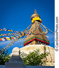 Buddhist Shrine Boudhanath Stupa with pray flags over blue...
