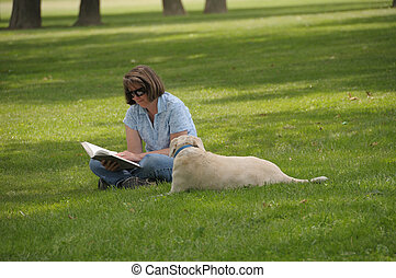 Woman Reading At The Park - Woman sitting on the lawn...