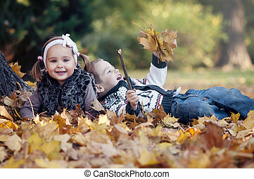 Happy little kids in autumn park