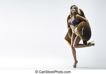 Young sexy woman in underwear stands with a teddy bear