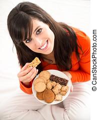 Eating sweet food in bed - Cute brunette woman eating sweet...