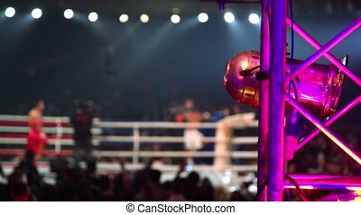 Fighters on boxing ring unfocused, light projector shell on...