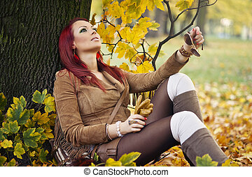 Portrait of a gorgeous woman reading a book in the autumn park.