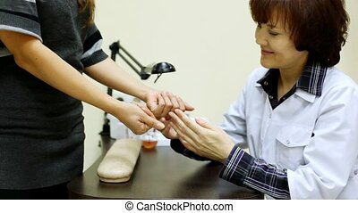 Cosmetician advises client and examine hands in salon -...
