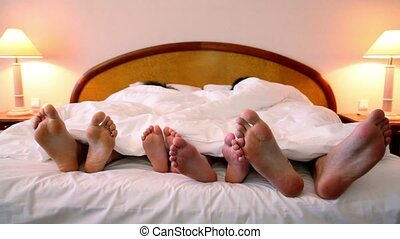 Four people lay in bed under blanket and move bootless feet,...