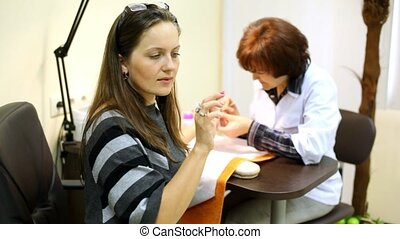 Technician of manicure finish manicure and checks all nails