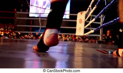 Fighter jumps on boxing ring, only legs are visible