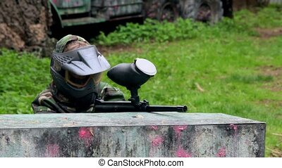 Boy paintball player sits in ambush behind metal fence