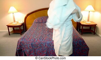 Woman in white bathrobe comes to bedroom and wipe her hair...