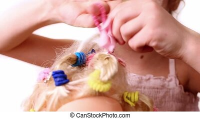 Little girl use elastic band to braid dolls hair, closeup...
