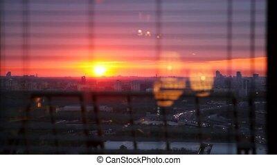 Sunset and flow of cars is visible from window at night...