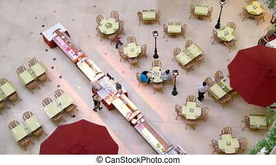 People walk and sit at tables in cafe, view from above
