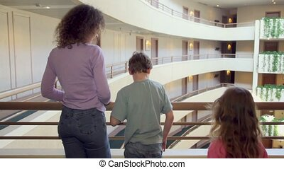 Mother and two her kids stand on balcony in multiple floor building