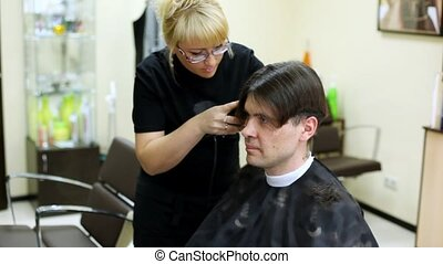 Hairdresser cuts hair to man with long hair - Hairdresser...