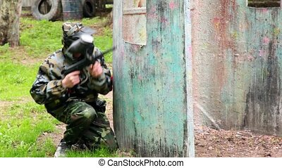 Boy paintball player sits in ambush behind metal fence and looks around