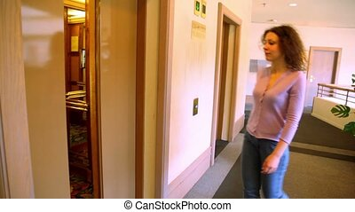 Automatic doors opens and young woman comes in elevator