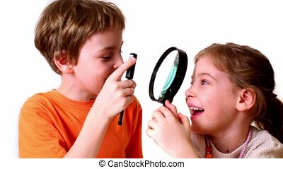 Two kids boy and girl play with magnifying glass isolated