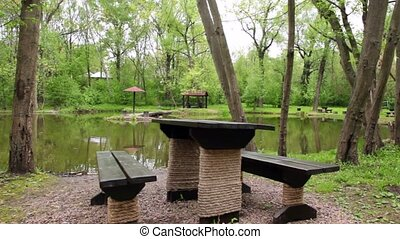 Table and benches ashore of small pond at summer, shown in...