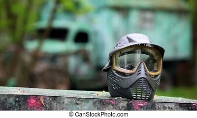 Boy comes closer to helm for paintball at background of blue...