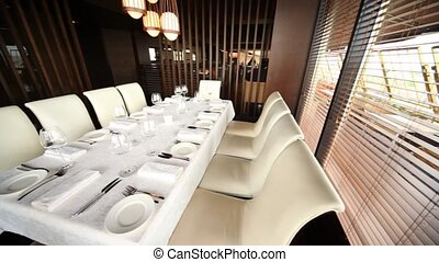 Decorated table  for ten persons stands in corner of hall of restaurant