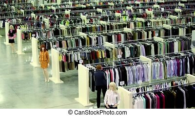 Customer watch goods inside clothes shop with mannequins -...