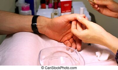 Manicure technician does to man of manicure also grinds skin...