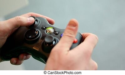 Man plays with colorful gamepad in his hand, closeup view
