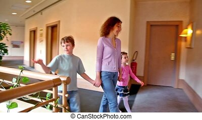 Mother with two kids walk along corridor