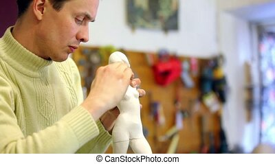 Sculptor corrects neck of armless female figurine, at background of tools