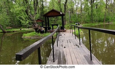 Bridge to summer house on small island on pond in grove