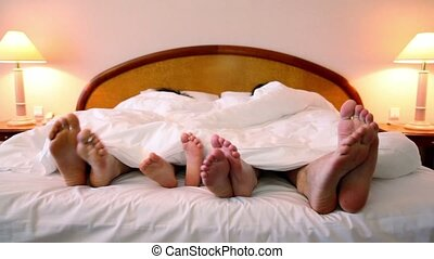 Parents and their kids lay in bed under blanket and move bootless feet