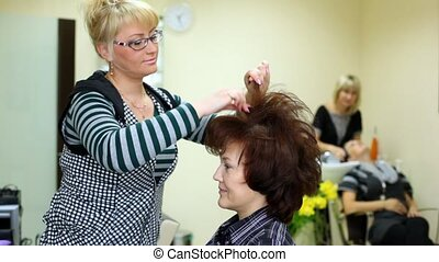 To woman of average years hairdresser does hairdress and fasten her by varnish