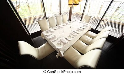 Table for ten persons stands in corner of hall of restaurant near to windows with view on terrace