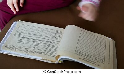 Little girl turns over pages of medical chart, only hands...