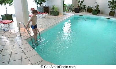 Little boy jumps to water from stairs at indoor pool