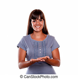 Smiling young female looking at you with hands up