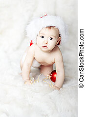 Christmas baby in red Santa Claus over white fur go on hands...