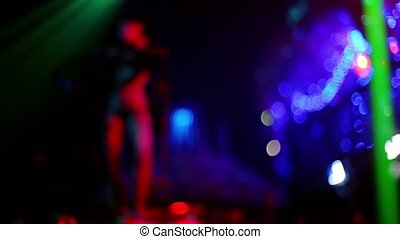 Almost nude woman dance in night club, unfocused view