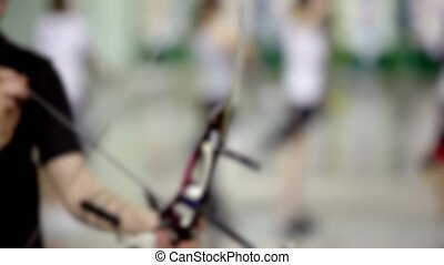 Few archers shoot in light room, unfocused sideview closeup