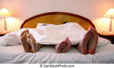 Parents with their son lay in bed under blanket and move bootless feet