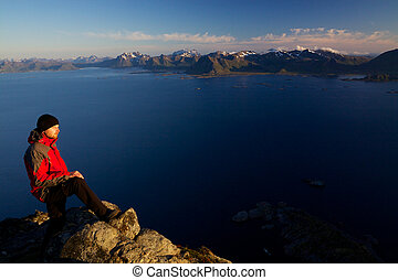 Picturesque summit in Norway - Active young man standing on...