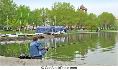 Fisherman on pond in city park at background of church behind trees