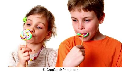 Two kids boy and girl eat lollipops isolated on white...