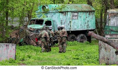 Five men paintball team walk to old truck