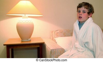 Little boy in white bathrobe sit and yawns before lay to...