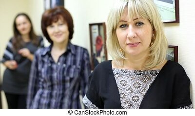 woman working in beauty salon affably looks and smiles -...