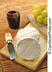 Italian tomino cheese on a wooden chopping board